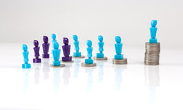 Leadership and corporate structure concept. Portrayed with male and femail figurines and coins. Money distribution concept. Fair pay Royalty Free Stock Photo