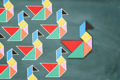 Leadership and creativity concept with tangram puzzle bird leadi Stock Photos