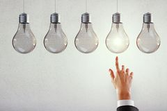 Leadership, idea and innovation concept. Hand pointing at row of illuminated light bulbs on subtle background. Leadership, idea and innovation concept royalty free stock images