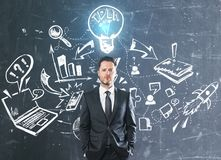 Leadership and innovation concept. Handsome young businessman standing on concrete wall background with creative business sketch. Leadership and innovation Royalty Free Stock Images