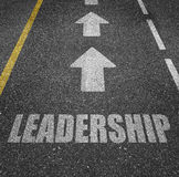 Leadership marked on a tarmac road. Text 'leadership' in white (gray) uppercase letters inscribed on a tarmac road with large white arrows above suggesting royalty free stock photo