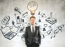Leadership and marketing concept. Handsome young businessman standing on concrete wall background with creative business sketch. Leadership and marketing concept Royalty Free Stock Photo