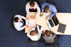 Leadership - mentoring. Businesspeople gathered around a table for a meeting, brainstorming. Aerial shot taken from directly above the table stock images