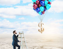 Leadership, money, win lottery concept. Businessman on ladder looking at golden dollar sign tied to balloons in bright sky with clouds. Leadership, money, win Royalty Free Stock Image