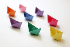 Leadership. Paper boats of multi-colour following a leader boat concept for leadership, teamwork and winning success royalty free stock photography