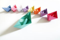 Leadership. Paper boats of multi-colour following a leader boat concept for leadership, teamwork and winning success Royalty Free Stock Photo