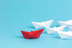 Leadership paper ship. Leadership concept with red paper ship leading among white on blue background with copy space. Business leadership concept. Minimal style Royalty Free Stock Photos