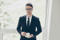 Leadership profession people  confidence concept. Portrait of ha. Ndsome attractive stylish trendy fashionable dressed in black suit business person holding cup Royalty Free Stock Image