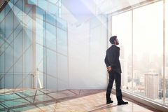 Leadership, success, research and future concept. Businessman looking out of window on abstract modern office city background. Double exposure stock photos