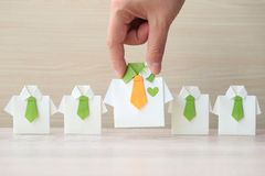 Leadership and teamwork concept, Woman hand holding origami yellow shirt with tie and leading among small yellow shirt on wooder stock image