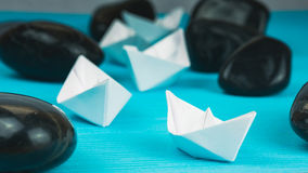 Leadership white paper boat lead further ships between abstract rock stones on blue background. Vintage Look.  Royalty Free Stock Photography