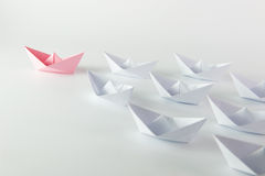 Leadership. Woman leadership concept with pink paper ship leading among white Stock Images