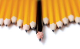 Leading. Low angle shot of Uneven row of yellow pencils with one black pencil in middle standing out farther than the rest. Focus is on the tip of the black Royalty Free Stock Photo