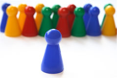 Leading. A single blue figurine in front of rows of other figurines, symbolizing concepts of leadership, but also facing the crowds, speaking to crowds, holding Stock Photography