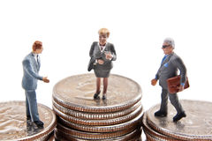 Leading Businesswoman. Miniature businesswoman gesturing to herself while standing on stack of quarters higher than male businessmen Royalty Free Stock Image