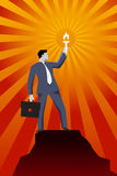 Leading in the darkness business concept. Successful businessman in business suit with case and burning torch on the top of the mountain, looking around and Royalty Free Stock Photos