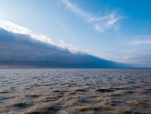 Leading edge with storm clouds of cold weather front approaching. Leading edge with line of storm clouds of cold weather front approaching blue sky on rough royalty free stock photos