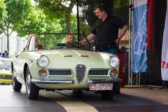 Leading exhibition takes interview driver Italian car Alfa Romeo Giulietta Spider Stock Image
