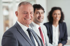 Leading a great team of young executives. Portrait of a diverse group of smiling businesspeople sitting in a row together at a table in an office boardroom stock images