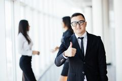 Leading my team to success. Handsome young businessman in smart casual wear keeping thumbs up and smiling while his colleagues tal royalty free stock image