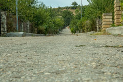 Leading old rough road in a caucasus village Royalty Free Stock Photography