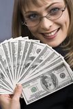 Leading into temptation. Smiling girl fanning herself with of bank notes Royalty Free Stock Photos