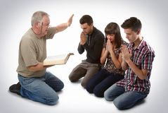Leading three people to Christ. Preacher leading three young souls in prayer to receive Jesus Stock Photo
