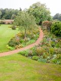 Leading walking path through garden in summer overcast scene royalty free stock images