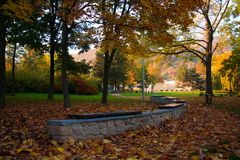 The leading walking path in the Krupka Park. With unique curved benches to relax by children playground Royalty Free Stock Image