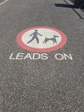 Leads on dog pavement sign.