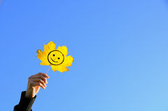 Leaf. Smile painted on an autumn leaf in his hand, raised to the sky royalty free stock photos