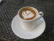A leaf in a Cappuccino. A cup of cappuccino with a leaf drawing Royalty Free Stock Images