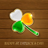 Leaf clover in Irish flag colors on wooden background Royalty Free Stock Images