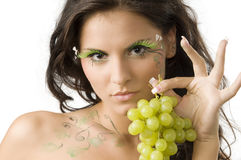Leaf and eyelashes. Pretty and sensual girl with bodypaint and eyelashes showing grape with hand Stock Photography