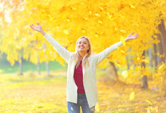 Leaf fall, happy expression young woman having fun in warm sunny autumn Stock Photos