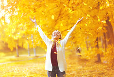 Leaf fall, happy expression young woman having fun in warm sunny autumn Royalty Free Stock Photo