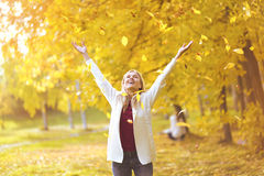 Leaf fall, happy woman in the autumn park