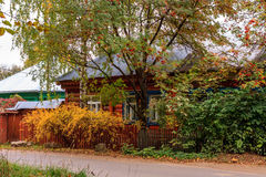 Leaf fall house. Old wood house surrounded by trees and yellow shrubs near the road in autumn Stock Photo