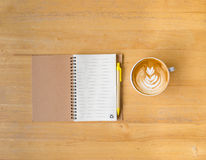 Leaf latte art coffee and notebook with pen Royalty Free Stock Photography