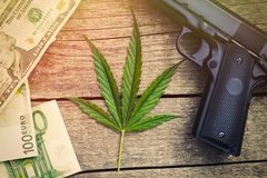 Leaf of marihuana with gun and banknotes. On wooden background Stock Photography