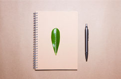 Leaf on notebook and pen on a brown paper. View from above. Stock Image