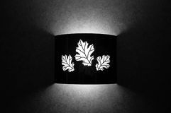 Leaf pattern light. Black and white image of a light attached to a wall with leaf patterns on it Stock Photography