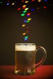 Leaf shape bokeh lights floating out of beer glass Stock Images