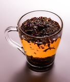 Leaf tea with herbs brewed in a glass cup. Close-up. Warm white brown tones. stock photography
