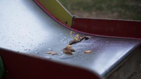Leaf of trees on wet children slide in park. Nature. Nobody. Leaf. Playground stock video