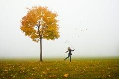 Leafes de travamento do outono da rapariga feliz imagem de stock royalty free