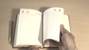 Leafing through a business book. Flipping through a business book with both hands stock video