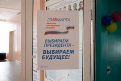 Leaflet hangs on the glass door at the polling station. BELOGORSK,KEMEROVO REGION, RF-March 18,2018: Broadsheet hangs on the glass door at the polling station Royalty Free Stock Image