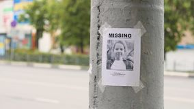 Leaflet about the missing child hanging on a pole,slow mo