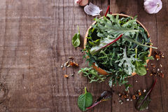 Leafy green mix over rustic wooden background with copy cpase Stock Photography